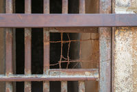 Closeup of a closed rusted iron bars of cell door in closed abandoned prison
