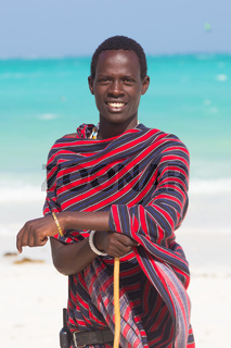 Traditonaly dressed maasai black man on picture perfect tropical Paje beach, Zanzibar, Tanzania, East Africa.