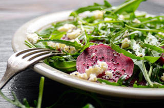 Clay dish with beetroot arugula and feta cheese salad on slate stone tray closeup view. Fork aside