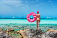 Young woman with pink donut swim ring on the stone in the sea