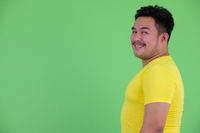 Profile view of happy young overweight Asian man smiling