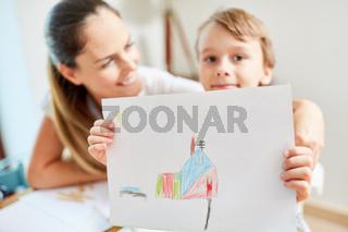 Kind mit Zeichnung vom Traumhaus