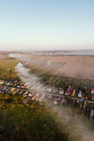 Aerial view of traditional Ukrainian village. Smoke spreads through the village. Early autumn