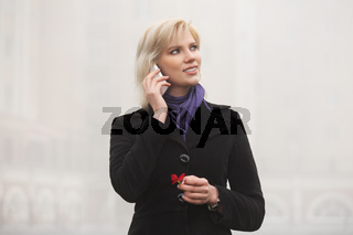 Young fashion woman talking on mobile phone walking in a city street