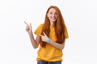 Photo of happy young woman standing isolated over white wall background. Looking camera showing copyspace pointing