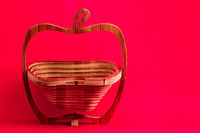 Decorative wooden lazer cut bread or fruit basket on pink background