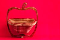Decorative wooden lazer cut bread or fruit basket on pink background