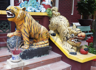 Tiger and lion statues at the entrance of a temple