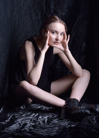 Sitting beautiful woman in black top and shoes  in dark studio.