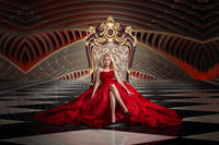 A woman in a luxurious gown dress sitting on a queen's throne