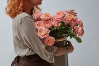 Red-haired girl florist holding a bouquet of pink roses in a vase on a gray background with copy space. The concept of a flower shop