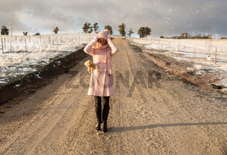 Happy go lucky woman walking down dirt road in light snow fall