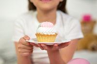 Cute girl eating cupcake.