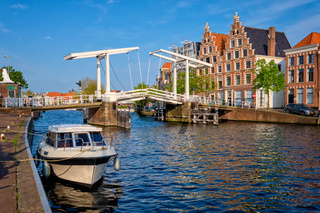 Spaarne river with boat and Gravestenenbrug bridge in Haarlem, Netherlands