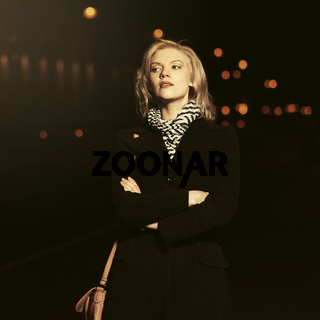 Fashion blond woman in black coat walking in night city street