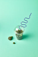 Healthy green organic raw broccoli florets in a plastic cup with straw on a green pastel background.