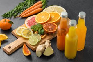 glass bottles of fruit juice on slate table top