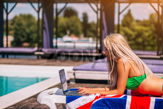 Concentrated Blondie Young Woman Is Laying On The Deck Chair And Typing On Her Laptop Near The Pool.