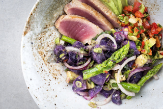 Modern fried tuna fish sashimi filet salad with green asparagus blue potatoes und vegetable chili relish as top view on a plate with copy space