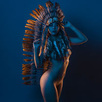 colored gels, beautiful blonde woman with indian feather plume on her head, is formed by brown feathers