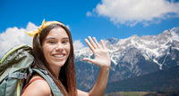smiling woman with backpack over alps mountains