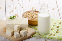 Non-dairy alternatives Soy milk or yogurt in glass bottle and tofu on white wooden table with soybeans in bowl aside