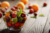 Assorted fruits in glass bowl on kitchen wooden table