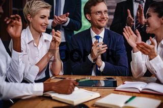 Happy businesspeople clapping hands at the meeting