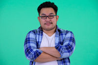 Young overweight Asian hipster man with arms crossed