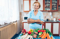 Happy senior woman at home with fresh crop from her garden