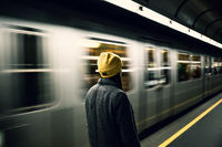 Young woman waits at the metro station while the train arrrives. Transportation and travel concept.