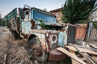 Old Truck Abandoned in front of a Village Backyard Wall