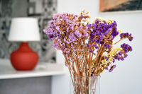 Pretty violet flowers in glass vase at home