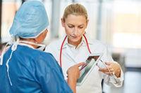 Chirurgin mit Tablet Computer und Kollegin