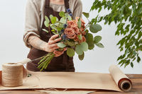 Young woman florist is making bouquet with fresh flowers roses living coral color at the table with paper and rope. Process step by step. Concept floral shop.