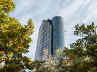 Main Tower Skyscraper low angle with trees in forefront on a sunny day, Frankfurt, Hessen, Germany
