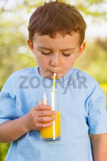 Kind kleiner Junge trinkt Orangensaft Saft trinken Hochformat draußen Frühling