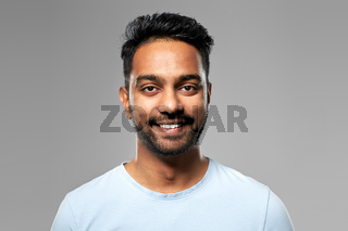 smiling young indian man over grey background