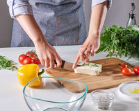 Woman's hands cut the cheese with the sprouts on the wooden board on the kitchen table with different vegetables. Step by step cooking healthy salad