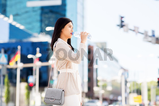 asian woman drinking water from bottle in city