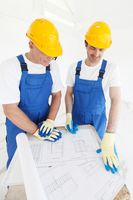 Builders in hardhats with blueprint