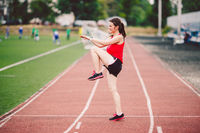 Female athlete preparing legs for cardio workout. Fitness runner doing warm-up routine. woman runner warm up outdoor. athlete stretching and warming up on a running track in a stadium