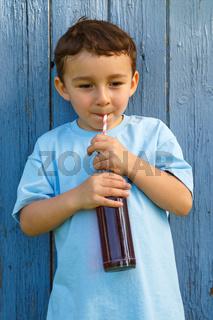 Kind kleiner Junge trinkt Cola Limonade trinken Hochformat draußen