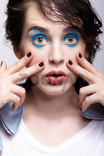 Portrait of female in blue jacket. Woman with unusual beauty makeup and wet hair, and blue shadows make-up.