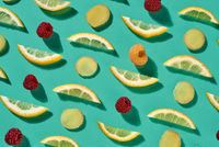 Fresh organic pattern from pieces of lemon and raspberry for healthy tea on a blue background. Food background. Flat lay