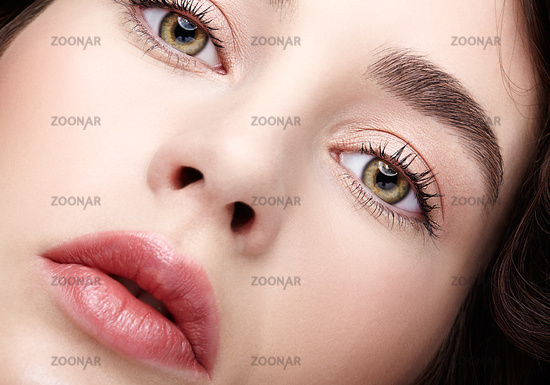 Closeup beauty macro face portrait of young woman. Brunette girl with day nude female makeup