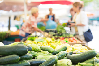 Blured unrecodnised people buying homegrown vegetable at farmers' market stall with variety of organic vegetable.