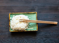 boiled rice with chopsticks on plate on dark table