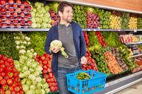 Junger Mann mit Einkaufskorb beim Gemüse Kauf