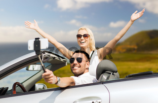 happy couple in car taking selfie by smartphone